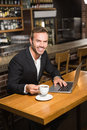 Handsome man using laptop and having a coffee in pub Royalty Free Stock Images