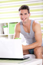 Handsome man using laptop smiling in his bedroom Stock Images
