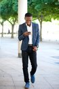 Handsome man walking and sending text message on cellphone Royalty Free Stock Photo