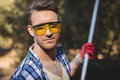 Handsome man wearing eyeglasses while using olive rake at farm Royalty Free Stock Photo