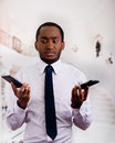 Handsome man wearing shirt and tie holding up two mobile phones with stressed facial expression Royalty Free Stock Photo