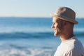 Handsome man wearing straw hat looking at the sea on beach Stock Photography