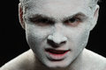 Handsome man with a white powder on the face frozen and mystical conceptual closeup photo of young aggressive evil looking covered Stock Photography