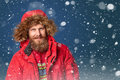 Handsome man in winter snow bearded wearing red jacket with hood on Stock Photo