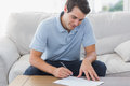 Handsome man writing on a paper in the living room Royalty Free Stock Image