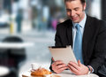 Handsome manager reviewing business updates corporate male on his tablet device Stock Photography
