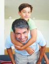 Handsome mature father piggybacking his son Stock Photo