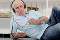 Handsome mature man listening to music with headphones Royalty Free Stock Photo