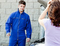 Handsome mechanic at garage with desperate woman Royalty Free Stock Photo