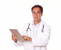 Handsome medical doctor using his tablet pc a portrait of a on white coat while standing and looking at you on isolated studio Royalty Free Stock Image
