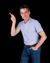 Handsome middle age man pointing at something black background Stock Images