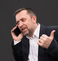 Handsome middle aged business man speaks mobile phone gesturing Stock Images