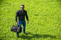 Handsome muscular hunk man outdoor in city park during daytime wearing black shirt and sunglasses Stock Images