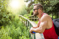 Handsome muscular hunk man outdoor in city park during daytime wearing tanktop and sunglasses Stock Photography