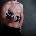 Handsome muscular male model doing exercise for biceps with dumbbells Stock Photo