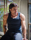 Handsome muscular man sitting on open window attractive looking down wearing dark tanktop Royalty Free Stock Photos