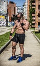 Handsome muscular shirtless hunk man outdoor in city setting showing healthy body while looking away Stock Photo