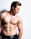 Handsome muscular young man looking sideways posing at studio on a white background with contrast shadows Stock Image