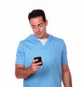 Handsome nurse guy texting with his cellphone portrait of a on blue uniform while standing on isolated studio Stock Photography