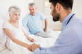 Handsome nurse holding hand of mature woman women at home Royalty Free Stock Photography