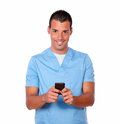 Handsome nurse man texting with his cellphone portrait of a on blue uniform while standing and smiling at you on isolated Royalty Free Stock Photo