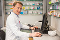 Handsome pharmacist using the computer at hospital pharmacy Royalty Free Stock Images