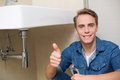 Handsome plumber gesturing thumbs up besides washbasin portrait of a in bathroom Royalty Free Stock Photos