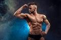 Handsome power athletic man bodybuilder. Wet Fitness muscular body on dark smoke background. Royalty Free Stock Photo