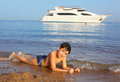 Handsome preteen sun tanned boy swimming on the res sea beach an and yaht background Royalty Free Stock Image