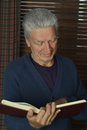 Handsome retired man reading book porhandsome booktrait of Stock Images
