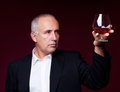Handsome senior man holding old brandy glass Royalty Free Stock Photography