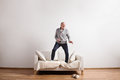 Handsome senior man standing on couch, dancing. Studio shot. Royalty Free Stock Photo