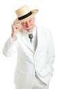 Handsome senior southern gentleman in a white suit and string tie tipping his straw hat politely isolated on white Stock Images