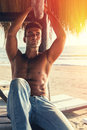 Handsome sexy male outdoor beach italian model man a shirtless in jeans relaxed seaside sunset and warm lighting concept of beauty Royalty Free Stock Photos