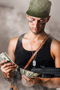 Handsome sexy military man with automatic counting the money Stock Photo
