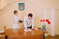 Handsome smiling groom signing wedding certificate at  ceremony in registry office Royalty Free Stock Photo