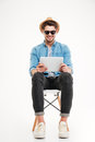 Handsome smiling male using tablet and sitting on the chair Royalty Free Stock Photo