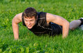 Handsome smiling man doing push ups at the park Royalty Free Stock Image