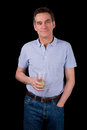 Handsome smiling middle age man holding drink black background Stock Photography