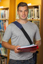 Handsome smiling student holding folder and notebooks in library Stock Image