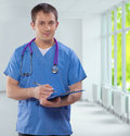 Handsome smiling young caucasian doctor wearing blue uniform hol holding clipboard writing in it and looking at camera Royalty Free Stock Photo