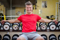 Handsome smiling young man in gym sitting on dumbbells rack and looking camera Stock Photography