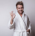 Handsome smiling young man in luxurious bathrobe photo Royalty Free Stock Images