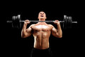 Handsome sportsman lifting a heavy weight on black background Stock Images