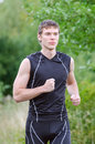 Handsome sportsman running in park Royalty Free Stock Photos