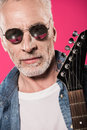 Handsome stylish senior man in sunglasses holding electric guitar Royalty Free Stock Photo