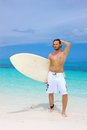 Handsome surfer posing with his surfboard and hand raised to hair in a sexy macho pose on a tropical beach against a blue Stock Image