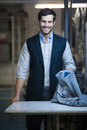 Handsome tailor man at work young smiling and checking clothes at the shop Royalty Free Stock Photos