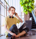 Handsome teenage boy talking by phone free feeling sitting on the floor in commercial center Stock Image