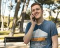 Photo : Handsome teenager talking on a mobile phone outdoors   reagents